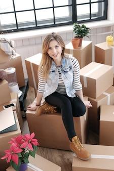 Frau fertig mit frachtpaketen und sitzt auf den kisten