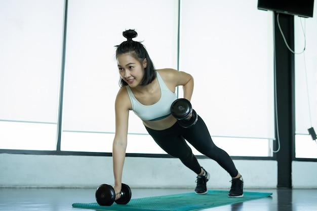 Frau fitnesstraining zu tun. eignungsfrau, die das handeln drückt, ups auf eine trainingsmatte. junge frau macht liegestütze im fitnessstudio. muskulöse frau, die liegestütze auf übungsmatte an der turnhalle tut.