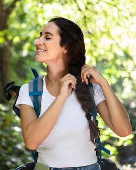 Frau flechtet ihr haar, während natur mit rucksack erkundet