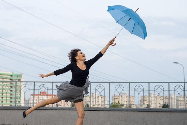 Frau fliegt mit regenschirm, hält regenschirm, stadtarthintergrund.