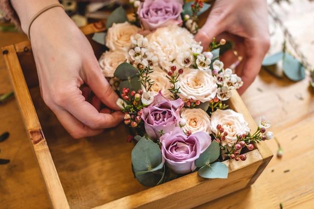 Frau florist sammelt eine blumenkomposition in einer holzkiste mit den händen