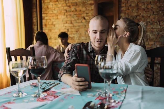 Frau flüstert ihrem freund im restaurant etwas ins ohr