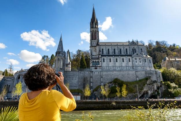 Frau fotografiert die kathedrale in lourdes, frankreich