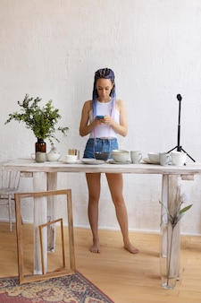 Frau fotografiert für ihr geschäft mit geschirr