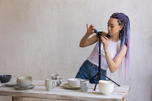 Frau fotografiert für ihr geschäft mit keramikgeschirr Kostenlose Fotos