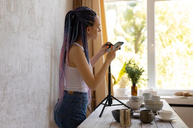 Frau fotografiert für ihr geschäft mit keramikgeschirr