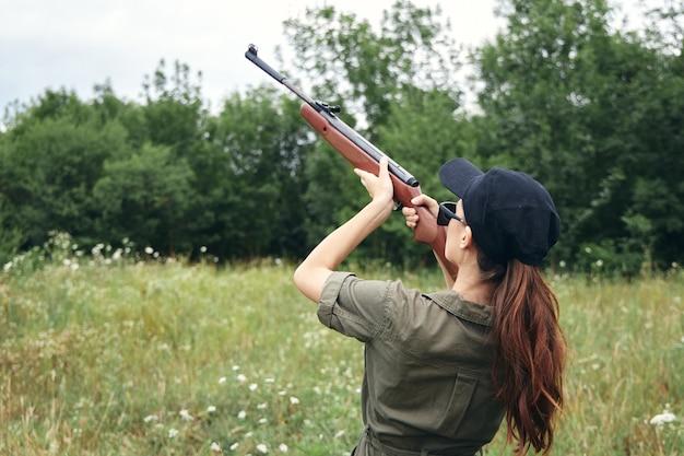 Frau frau, die eine waffe hält, die frisches luftgrün jagt