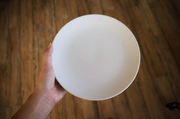 Frau (frau) hände halten (unterstützung) eine weiße schale (platte) auf holztisch.