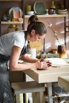 Frau freiberuflich, business, hobby. frau, die keramische tonwaren auf tabelle im studio macht