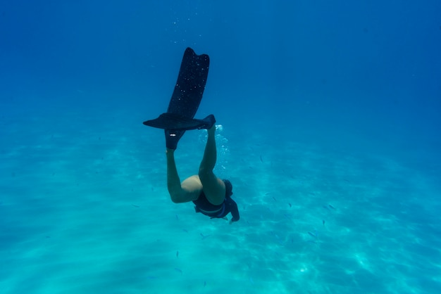 Frau freitauchen mit flossen unter wasser