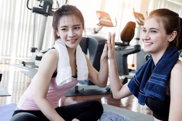 Frau freund in fitness health center woth stretch aktion pose auf yoga-matte