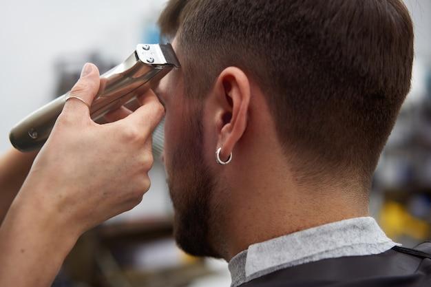 Frau friseur geschnitten haar schönen kaukasischen jungen mann
