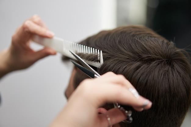 Frau friseur schneiden haar schönen kaukasischen mann in modernen friseursalon