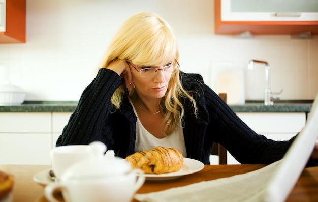 Frau frühstücken und zeitung lesen