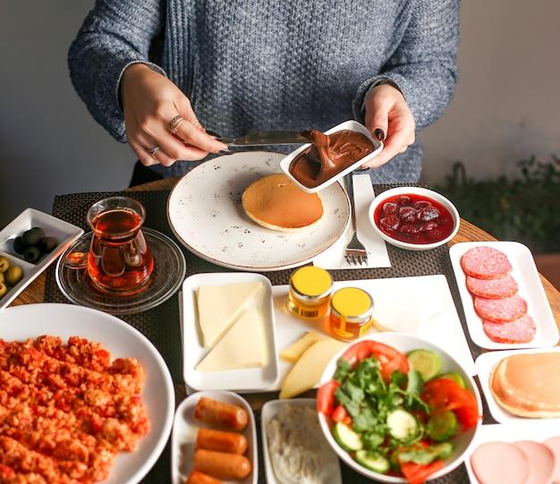 Frau frühstückt mit pfannkuchen und schokoladencreme
