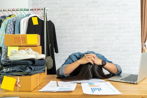 Frau frustriert erschöpft legte ihren kopf auf den tisch und verkaufte online