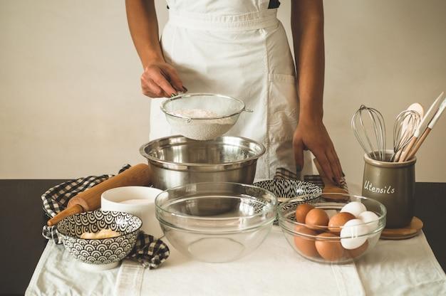 Frau fügt etwas mehl teig auf holztisch hinzu. frauenhände, die frischen teig kneten. konzept zutaten zum kochen von mehlprodukten oder teig. ländlicher oder rustikaler stil.