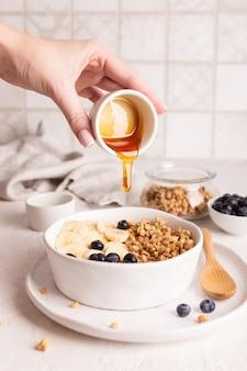Frau fügt müsli honig hinzu, gesundes frühstück mit müsli und früchten