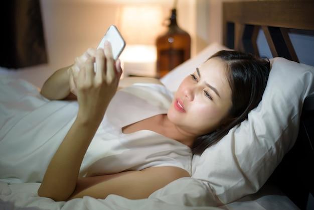 Frau fühlt augenschmerzen, wenn sie smartphone nachts benutzt