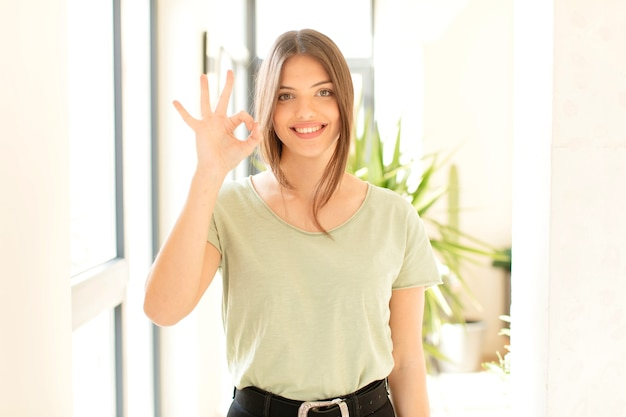 Frau fühlt sich glücklich, entspannt und zufrieden, zeigt zustimmung mit einer okayen geste, lächelt