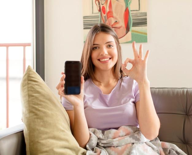 Frau fühlt sich glücklich, entspannt und zufrieden, zeigt zustimmung mit okayer geste, frau lächelt