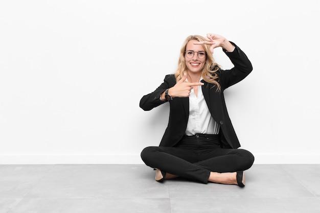 Frau fühlt sich glücklich, freundlich und positiv, lächelt und macht ein porträt oder einen fotorahmen mit den händen