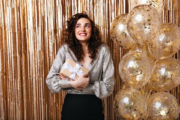 Frau fühlt sich glücklich und hält ihr geburtstagsgeschenk auf goldenem hintergrund