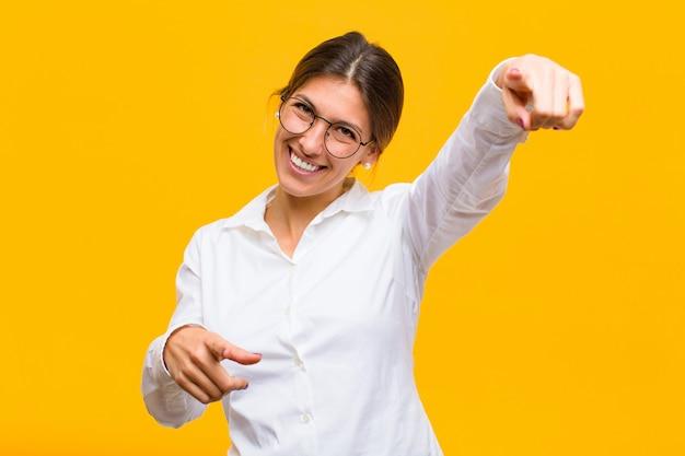 Frau fühlt sich glücklich und selbstbewusst, zeigt mit beiden händen und lacht, wählt dich