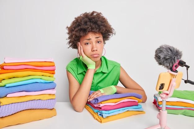 Frau fühlt sich müde, nachdem sie wäsche gefaltet hat, hat ihren eigenen blog über den häuslichen lebensstil sitzt am tisch vor der smartphone-kamera isoliert auf weiß Kostenlose Fotos