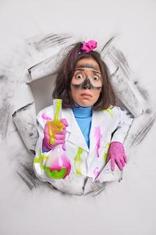 Frau führt chemische tests durch oder experiment hält flasche mit flüssigkeit schmutzig nach explosion beschäftigt im labor arbeitet trägt weißen kittel durchbricht papier