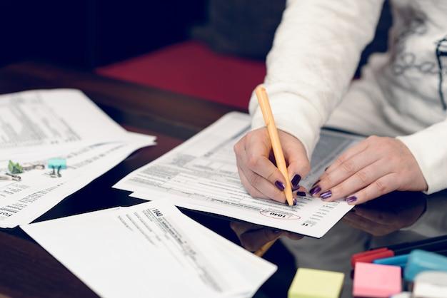 Frau füllt das steuerformular mit steuerdokumenten aus formular 1040 einkommensteuererklärung für einzelpersonen