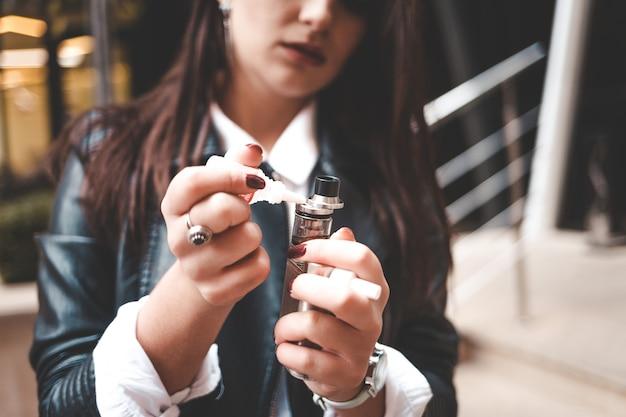 Frau füllt flüssigkeit in der e-zigaretten-nahaufnahme nach. mädchen füllt flüssigkeit im dampf nach. konzept der elektronischen zigarette