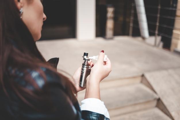 Frau füllt flüssigkeit in der e-zigaretten-nahaufnahme nach. mädchen füllt nach