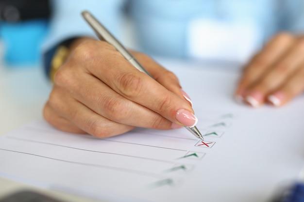 Frau füllt fragebogen aus, indem sie dokument ankreuzt.