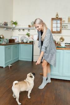 Frau füttert hund und hält eine tasse in ihrer küche.