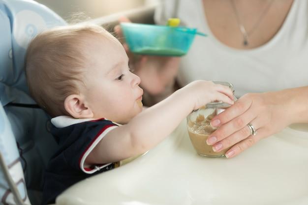 Frau füttert ihr baby vom löffel mit apfelmus