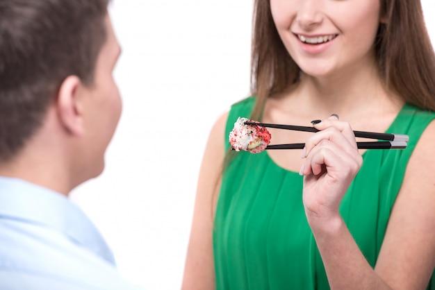 Frau füttert ihren freund mit sushi.