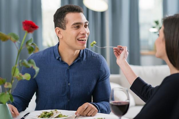 Frau füttert ihren mann bei einem romantischen abendessen