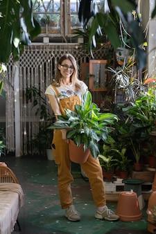 Frau gärtner halten zimmerpflanze lächelnd freiberufler mädchen florist im hausgarten gewächshaus oder laden
