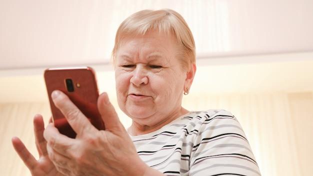 Frau gealtert mit einem mobilen gerät in ihren händen.