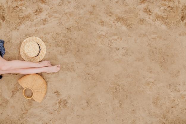 Frau gebräunte beine, strohhut und tasche am sandstrand. reisekonzept. entspannen sie am strand mit den füßen im sand.