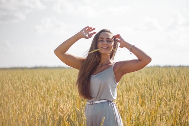 Frau gebräunte haut lange braune haare silber seidenkleid stehend auf einem feld