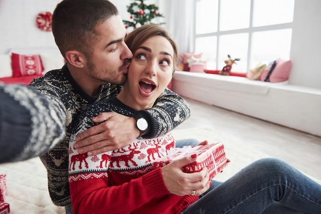 Frau geht an ihrem freund beim halten des geschenks spazieren. bemannen sie das nehmen von selfie von ihm und von seiner frau, die in der weihnachtskleidung gekleidet werden und auf dem boden des dekorativen schönen raumes sitzen