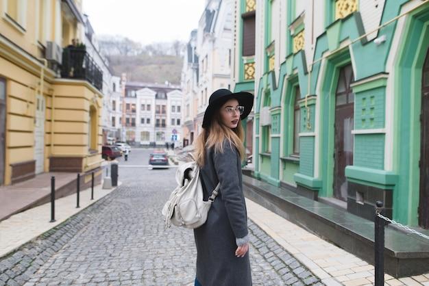 Frau geht durch die straßen der altstadt. stilvolles touristenmädchen, das in einer schönen stadt geht.