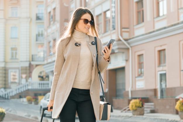 Frau geht entlang stadtstraße mit reisekoffer und -handy