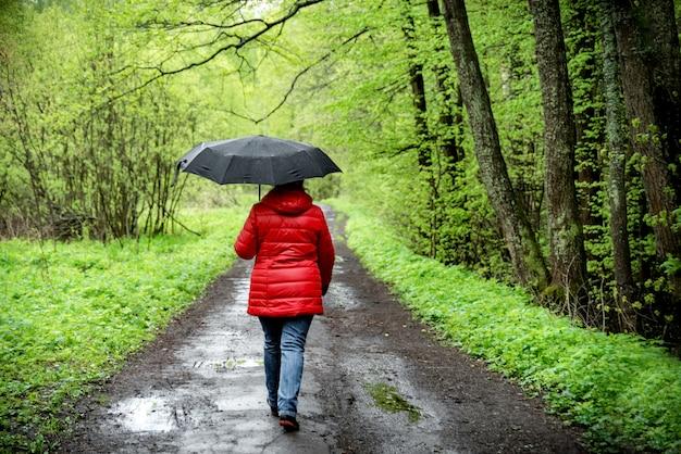 Frau geht im park unter einem regenschirm im regen