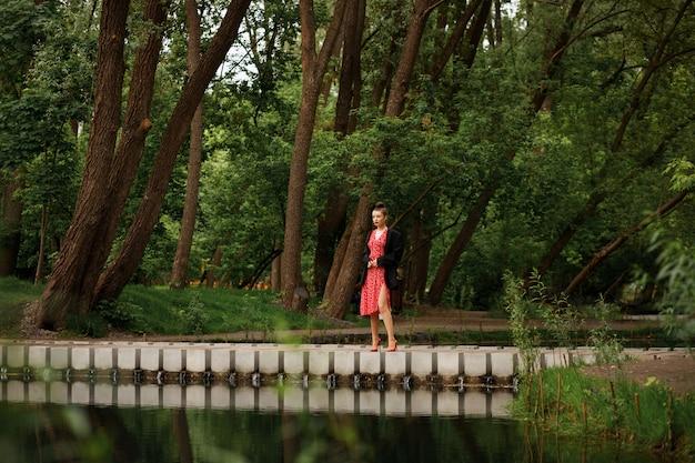 Frau geht im sommer in einem schönen stadtpark spazieren. nach dem regen gehen. rotes kleid, rote schuhe