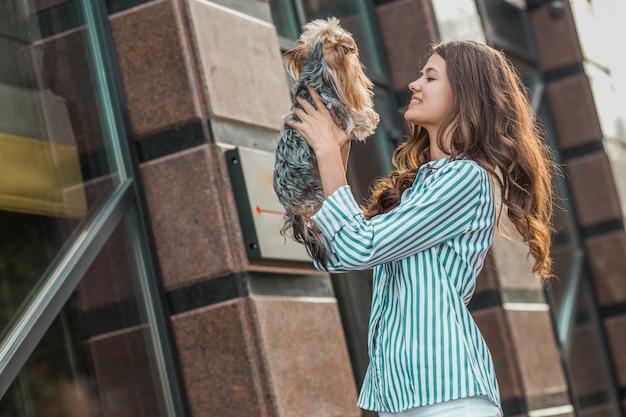 Frau geht mit einem hund in der stadtstraße.