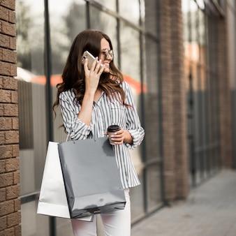Frau geht nach dem einkaufen und benutzt das telefon.