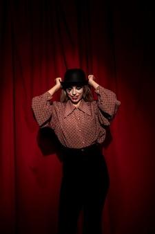 Frau gekleidet als clown, der ihren hut setzt